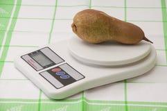 Birne auf einer digitalen Skala der weißen Küche Lizenzfreies Stockfoto
