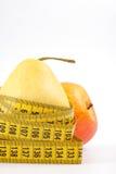 Birne und Apfel mit einem messenden Band Lizenzfreies Stockfoto