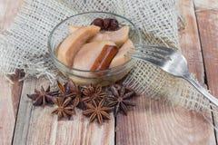Birnen-Kompott mit Gabel auf Holztisch mit Stern-Anis u. Cinnamo stockfotografie
