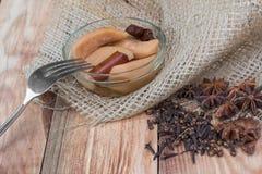 Birnen-Kompott mit Gabel auf Holztisch mit Stern-Anis u. Nelken lizenzfreies stockfoto