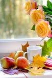 Birnen und gelbe Rosen mit Ahornblättern nähern sich Fenster stockbild