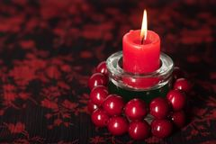 Birning candle with red beads Stock Photos