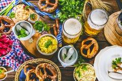 Birra bavarese con le ciambelline salate molli, il grano ed il luppolo su di legno rustico fotografie stock