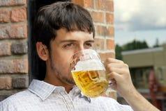 Birra bevente del giovane tirante Immagini Stock