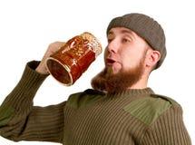 Birra bevente del tirante barbuto dal vetro Fotografie Stock