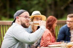 Birra bevente dell'uomo con gli amici al partito di estate Immagine Stock