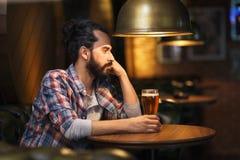 Birra bevente dell'uomo solo infelice alla barra o al pub immagine stock libera da diritti