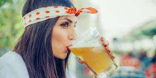 Birra bevente della bella giovane donna e godere del giorno di estate immagine stock