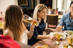 Birra bevente della giovane donna con gli amici Immagini Stock