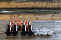 Birra in bottiglie sulla tavola con le verdure in un setaccio Fotografia Stock