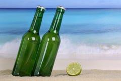 Birra in bottiglie verdi sulla spiaggia in sabbia Immagini Stock