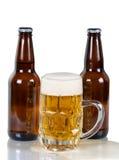 Birra che esce dalla tazza di vetro sulla superficie di vetro Fotografie Stock