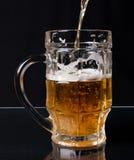 Birra che versa in una tazza Fotografia Stock