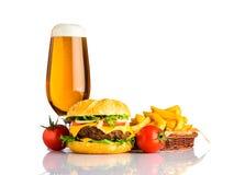 Birra, cheeseburger e patate fritte su fondo bianco Immagine Stock