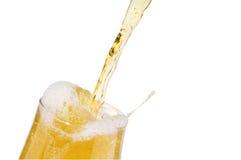 Birra chiara dell'alcool che versa in un vetro isolato fotografia stock