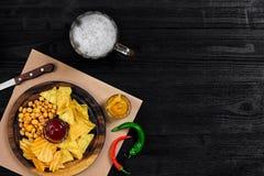 Birra chiara e spuntini sulla tavola di legno nera Dadi, chip Vista superiore con Copyspace Immagini Stock