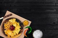 Birra chiara e spuntini sulla tavola di legno nera Dadi, chip Vista superiore con Copyspace Fotografie Stock Libere da Diritti