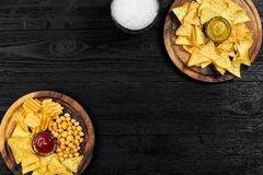 Birra chiara e spuntini sulla tavola di legno nera Dadi, chip Vista superiore con Copyspace Fotografia Stock Libera da Diritti