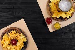 Birra chiara e spuntini sulla tavola di legno nera Dadi, chip Vista superiore con Copyspace Fotografia Stock