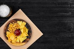 Birra chiara e spuntini sulla tavola di legno nera Dadi, chip Vista superiore con Copyspace Fotografie Stock