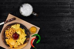 Birra chiara e spuntini sulla tavola di legno nera Dadi, chip Vista superiore con Copyspace Immagine Stock