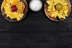 Birra chiara e spuntini sulla tavola di legno nera Dadi, chip Vista superiore con Copyspace Immagine Stock Libera da Diritti