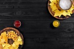 Birra chiara e spuntini sulla tavola di legno nera Dadi, chip Vista superiore con Copyspace Immagini Stock Libere da Diritti
