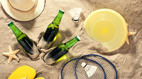 Birra chiara fredda con gli oggetti per le attività della spiaggia sulla sabbia Fotografia Stock
