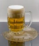 Birra chiara nella tazza su superficie bagnata Fotografia Stock