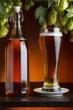 Birra con il luppolo sulla tavola di legno Fotografie Stock