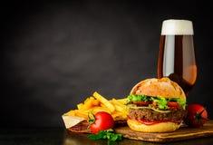 Birra con l'hamburger e le patate fritte sullo spazio della copia Immagini Stock Libere da Diritti