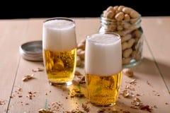Birra con le arachidi sulla vecchia tavola di legno immagine stock libera da diritti