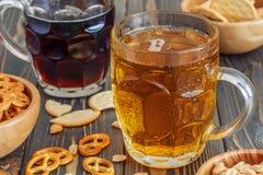 Birra con le ciambelline salate, i cracker ed i dadi Fotografie Stock Libere da Diritti