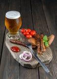 Birra con le salsiccie, i pomodori ciliegia e la cipolla Fotografie Stock Libere da Diritti