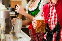 Birra del disegno della giovane donna in ristorante o in pub Fotografie Stock