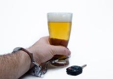 Birra della tenuta della mano con le manette e la chiave dell'automobile Fotografia Stock Libera da Diritti