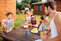 Birra di conversazione e bevente dei giovani sorridenti all'aperto Fotografia Stock Libera da Diritti