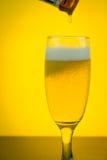Birra di versamento ad un vetro sul fondo giallo della lampadina Immagine Stock