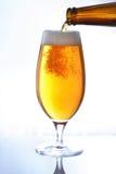 Birra di versamento dalla bottiglia Fotografia Stock