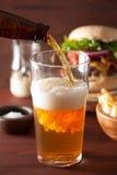 Birra di versamento della birra chiara dell'India nel vetro della pinta e negli alimenti a rapida preparazione Fotografia Stock