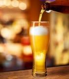Birra di versamento in vetro sullo scrittorio della barra Immagini Stock Libere da Diritti
