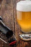 Birra di vetro con la bottiglia vuota sulla tavola di legno Immagini Stock