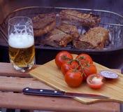 Birra e bistecche sulla griglia Fotografia Stock
