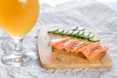 Birra e panino con il pesce spuntini messi sul bordo di legno fotografia stock
