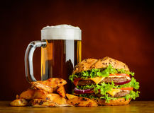 Birra fredda con l'hamburger e Fried Potatoes Fotografie Stock
