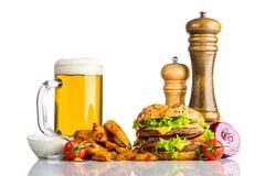 Birra fredda della tazza con le fritture e l'hamburger su fondo bianco Immagini Stock