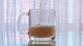 Birra fresca della schiuma che è versata in una tazza di birra Movimento lento video d archivio