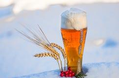 Birra leggera nella neve con le orecchie di grano Fotografie Stock