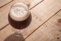 Birra scura su legno Fotografie Stock