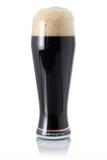 Birra scura in vetro con schiuma fotografia stock libera da diritti